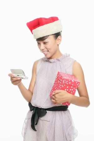 Woman with santa hat text messaging on the phone while holding present photo