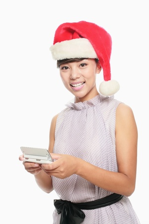 Woman with santa hat text messaging on the phone  photo
