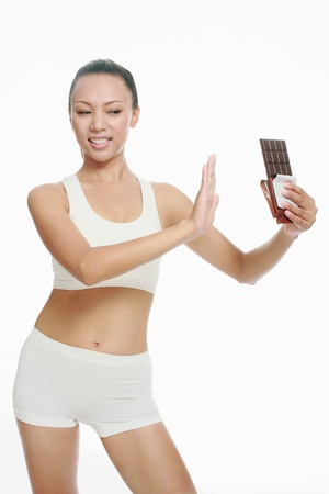 Woman restricting herself from eating a bar of chocolate photo