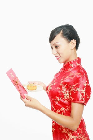 Woman reading greeting card while holding a plate of moon cake Stock Photo - 9605283