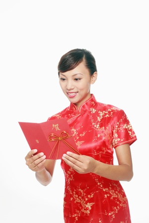 Woman in red cheongsam reading greeting card Stock Photo - 9605599