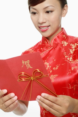 Woman in red cheongsam reading greeting card  Stock Photo - 9605315