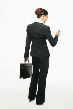 Businesswoman text messaging on the mobile phone photo