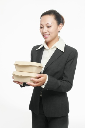 Businesswoman holding a stack of take out food photo