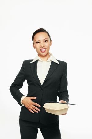 Businesswoman touching her  tummy while holding take out food photo