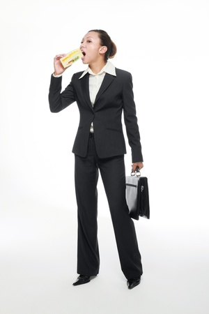 adult sandwich: Businesswoman carrying bag while eating sandwich