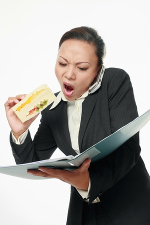 inconvenience: Businesswoman talking on the phone, eating and reading document at the same time