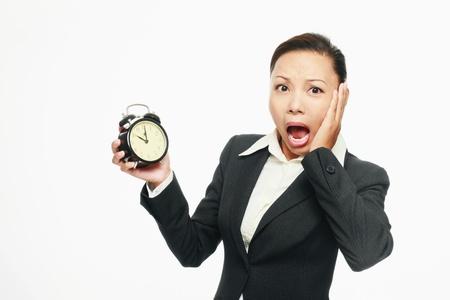 Businesswoman holding alarm clock photo