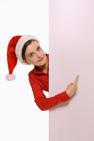 Businesswoman with santa hat pointing at white board Stock Photo - 9605738