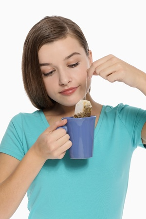 Woman dipping teabag into a cup of hot water photo