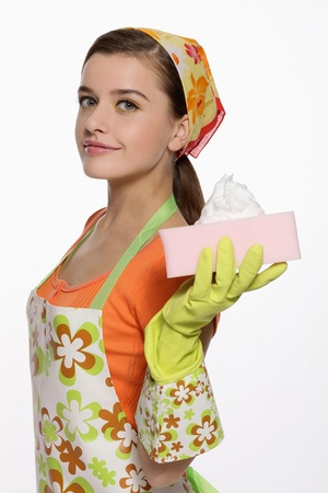 Woman in apron holding cleaning sponge photo