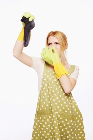 holding nose: Woman holding up a dirty sock
