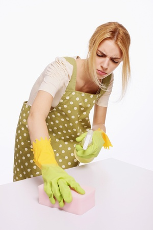 Woman spraying and wiping table photo