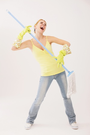 Woman using mop as guitar Stock Photo - 9605590