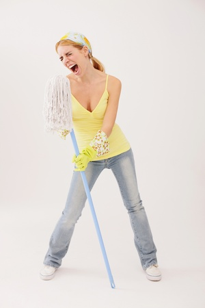 Woman using mop as microphone Stock Photo - 9605192