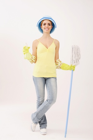 Woman with pail on head holding mop and spray bottle photo
