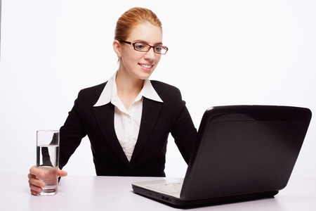 Businesswoman holding a glass of water while using laptop Stock Photo - 9605231