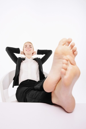 Businesswoman resting with her legs up on a table and hands behind her head photo