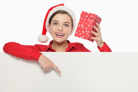 Businesswoman with santa hat holding present and pointing at white board photo