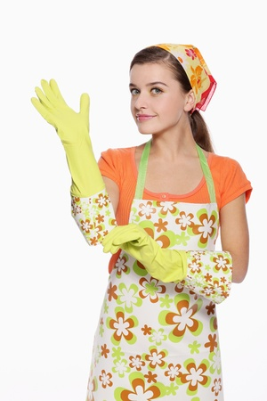 Woman in apron putting on rubber glove Stock Photo - 9678757