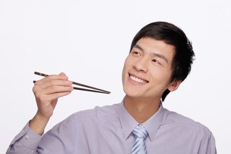Businessman eating with chopsticks photo