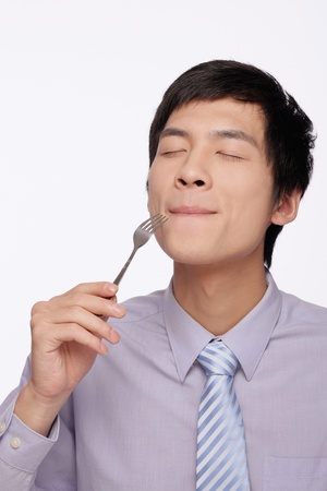 Businessman eating with fork