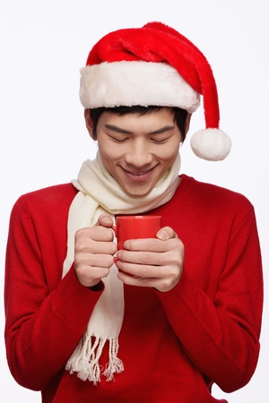 Man with santa hat holding a cup of hot coffee Stock Photo - 9678791
