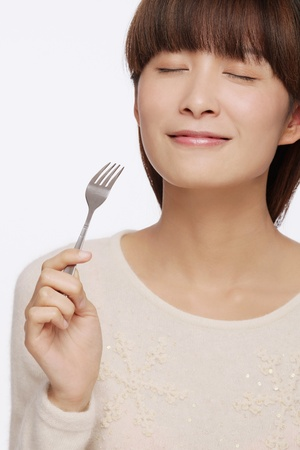 Woman eating with fork Stock Photo