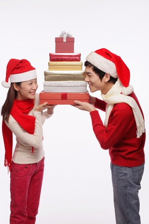 Man and woman holding a stack of gift boxes Stock Photo - 9678471