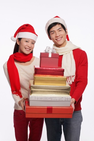 Man and woman holding a stack of gift boxes Stock Photo - 9678553