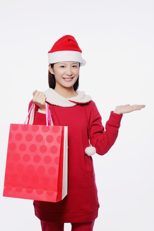 Woman with santa hat carrying shopping bags photo