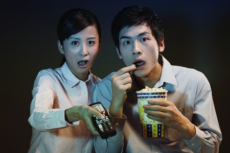 Man and woman watching horror movie on television photo