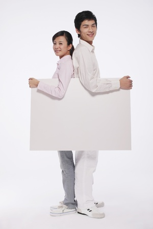 Man and woman holding white placard with their backs against each other Stock Photo - 9678342