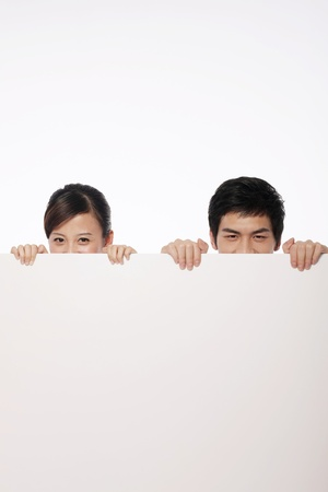Man and woman hiding behind a white placard photo