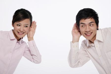 personas escuchando: Hombre y mujer con las manos sobre las orejas