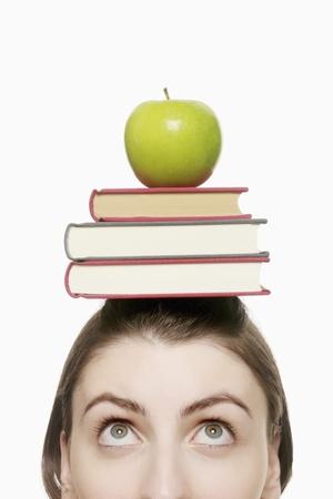 manzana verde: Equilibrio de una pila de libros y manzana verde en la cabeza de mujer Foto de archivo