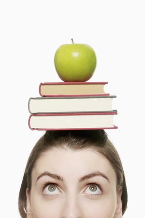 Woman balancing a stack of books and green apple on her head Stock Photo