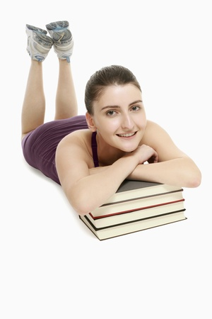 lying forward: Woman lying forward on the floor with her chin resting on a stack of books