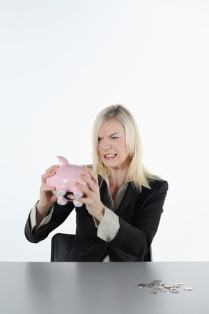 Businesswoman shaking piggy bank in frustration Stock Photo - 9900832
