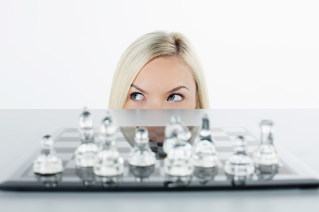 british ethnicity: Businesswoman peeking from under the table, chess set on the table
