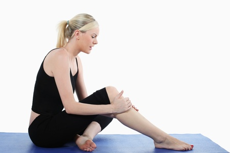sprain: Woman holding her knee while sitting on yoga mat