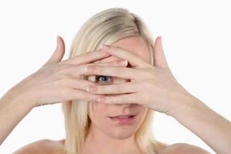 Woman peeking in between her fingers photo