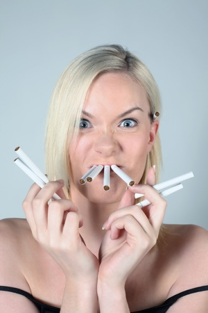 british ethnicity: Woman with cigarettes in her mouth and holding some in her hands