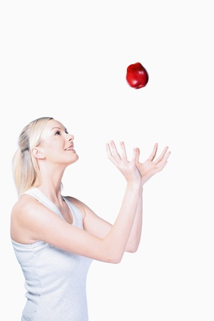 british ethnicity: Woman tossing apple in the air Stock Photo