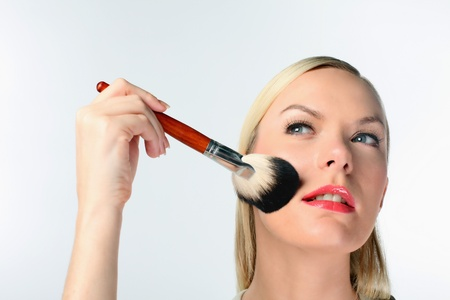 self conceit: Woman applying make-up on her face