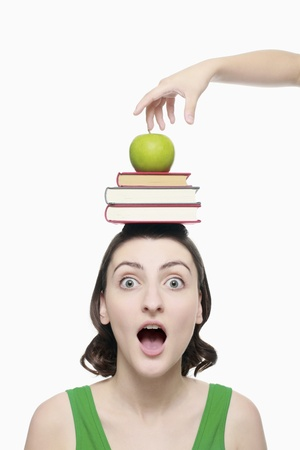Hand about to take apple from top of womans head, woman in shock photo