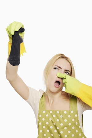 Woman holding up a dirty sock Stock Photo - 9957399