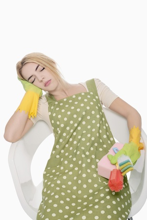 Woman holding cleaning products while sleeping on the chair Stock Photo - 9957535