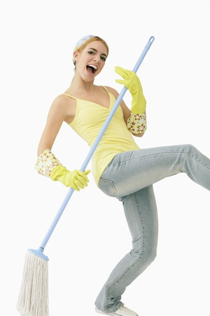 Woman using mop as guitar Stock Photo
