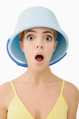Woman with pail on head looking shocked photo